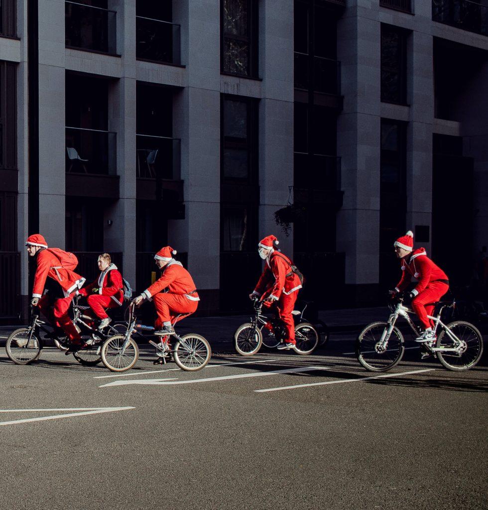 Kuvassa joulutonttuja pyöräilemässä.